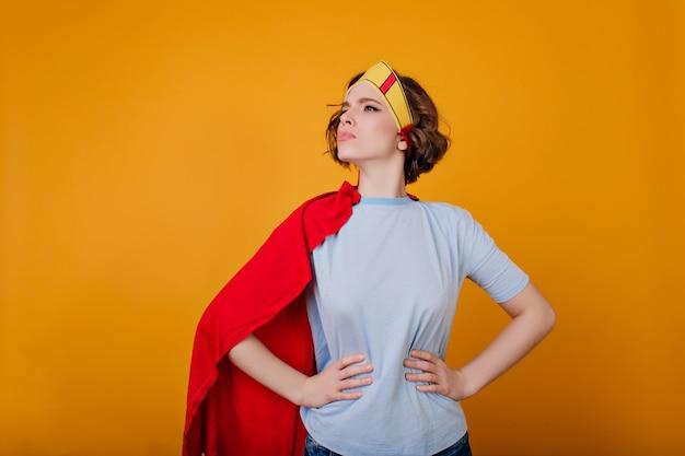 Ernsthafter weiblicher krieger im lustigen kostüm, das auf gelbem raum aufwirft