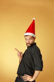 Ernsthafter weihnachtsmann, der eine weihnachtsmütze auf dem orangefarbenen studio trägt, das nach links zeigt