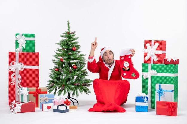 Ernsthafter weihnachtsmann, der oben zeigt, der auf dem boden sitzt und weihnachtssocke nahe geschenken und geschmücktem neujahrsbaum auf weißem hintergrund hält