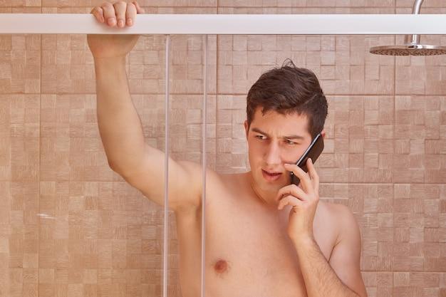 Ernsthafter weißer mann benutzt smartphone im badezimmer.