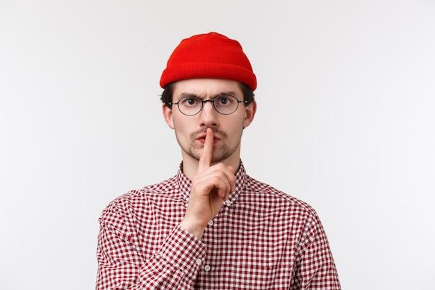 Ernsthafter wütender bärtiger kaukasischer mann, der enttäuscht und sauer vor ungehorsamen schülern, die zu laut sprechen, vor der kamera schweigt, mit zeigefinger gepressten lippen eine stille geste macht, die stirn runzelt und ruhig bleibt