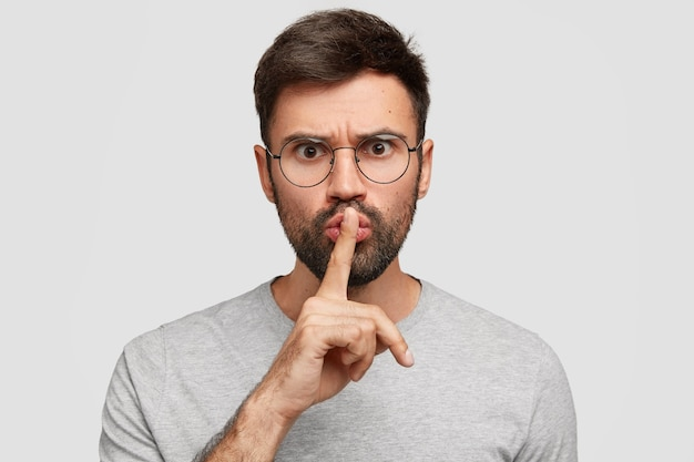 Ernsthafter wütender bärtiger mann hält zeigefinger über die lippen, fordert völlige stille