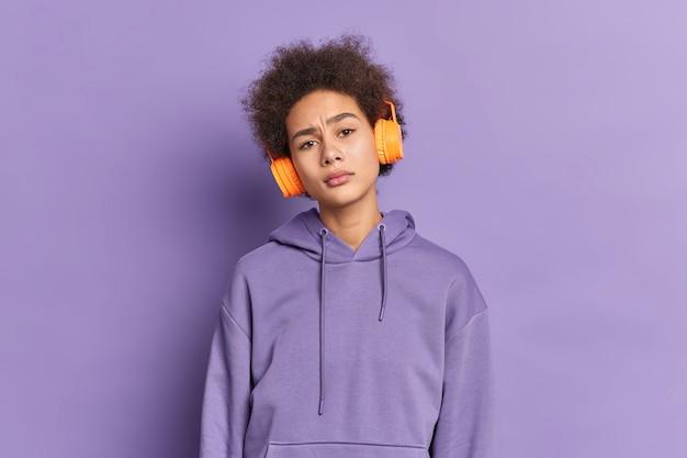 Ernsthaftes afroamerikanisches tausendjähriges mädchen hört audiospur über stereokopfhörer, hat lockiges buschiges haar trägt lila kapuzenpulli.