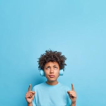 Ernsthaftes unzufriedenes afroamerikanisches mädchen mit lockigen haaren zeigt zeigefinger oben zeigt werbung gegen blaue wand hört musik über drahtlose kopfhörer, die mit dem hohen preis des produkts unzufrieden sind