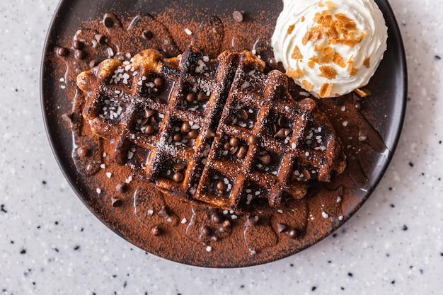 Ernte bild flach lag leckere hausgemachte belgische waffel mit dunklem schokoladensirup, kakaopulver und schokoladenstückchen, serviert mit schlagsahne in brauner farbtafel. delikatesse und stilvolle küche.