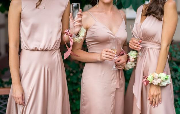 Ernte foto schöne schlanke brautjungfern warten auf den beginn der zeremonie. hochzeitslook, identische kleider und butannieres aus natürlichen blumen