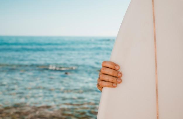 Ernte hand, die surfbrett hält