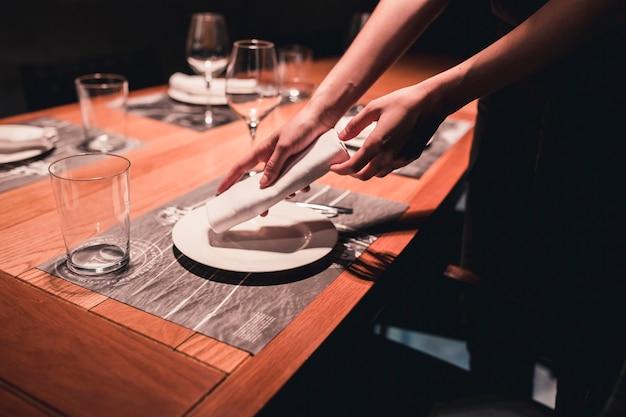 Ernte hostess putting napking auf platte