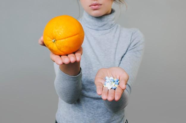 Ernte junge dame in bluse, die frisches orange und haufen des medikaments auf palmen auf grau zeigt