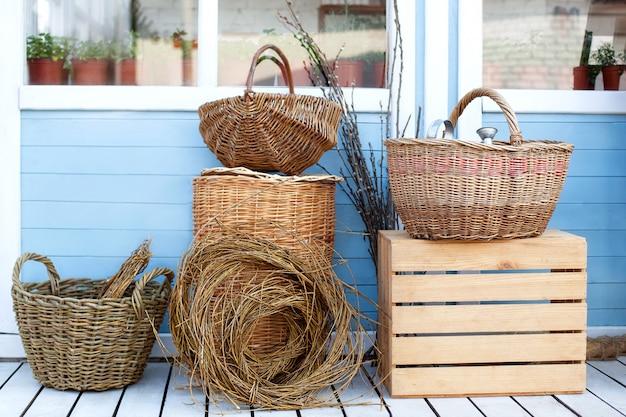 Ernte-konzept. herbstfrüchte in körben ernten. weidenkörbe gegen die wand eines blauen landhauses. rustikaler stil. gartenarbeit. herbsternte von viel. gartenarbeitkonzept. gemüse