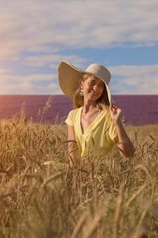 Ernte: reifer weizen wächst auf dem feld. das goldene korn und das mädchen gehen durch das feld. die heiße sonne streichelt die haut