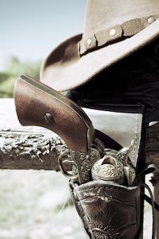 Ernte von cowboy-pistole und hut im freien unter sonnenlicht