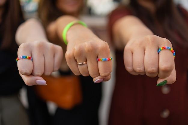 Ernte von drei mädchen, die ihre stylische maniküre zeigen, die ihre finger auf schwarzem lederhandtaschendiff...