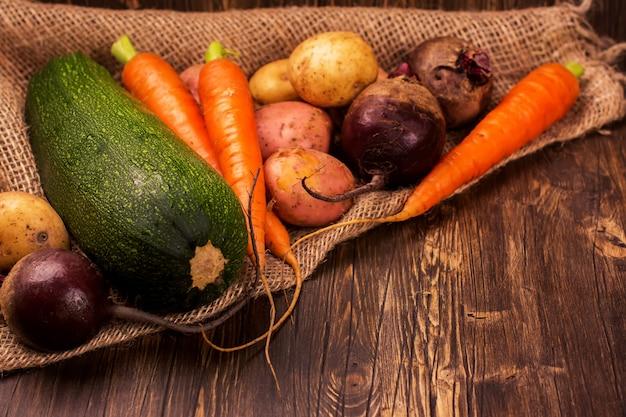 Erntefest. frisches organisches gemüse: karotte, kartoffel, zuckerrübe und eierkürbis auf rustikalem hölzernem hintergrund getontes bild