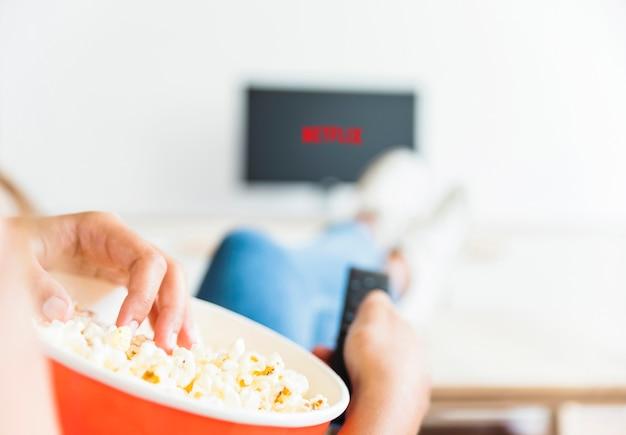 Erntefrau, die popcorn isst und serie im wohnzimmer aufpasst