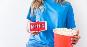 Erntefrau mit dem Popcorn, das Netflix-Logo auf Smartphone zeigt