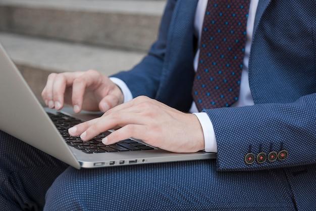 Erntegeschäftsmann, der auf laptoptastatur schreibt