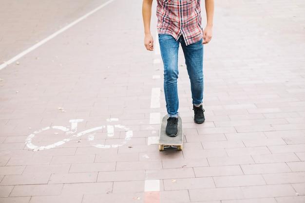 Erntejugendlicher, der nahe fahrradweg skateboard fährt