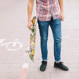 Erntejugendlicher mit skateboard nahe fahrradweg