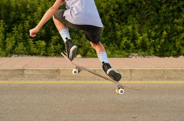 Erntejunge springt mit skateboard und zeigt trick