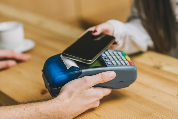 Erntekunde, der mit smartphone im café zahlt