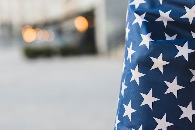 Ernten sie amerikanische flagge mit eingewickelter person