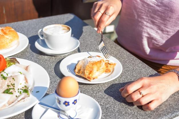 Ernten sie den schuss der frau ihr kontinentales frühstück essend