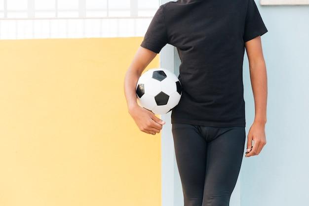 Ernten sie den schwarzen mann, der fußball steht und hält