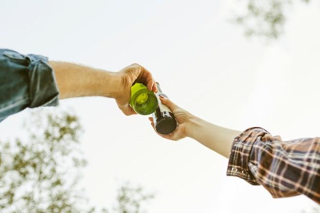 Ernten sie die hände, die flaschen in der natur klirren