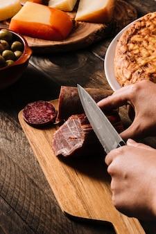 Ernten sie die hände, die geräuchertes fleisch nahe lebensmittel schneiden