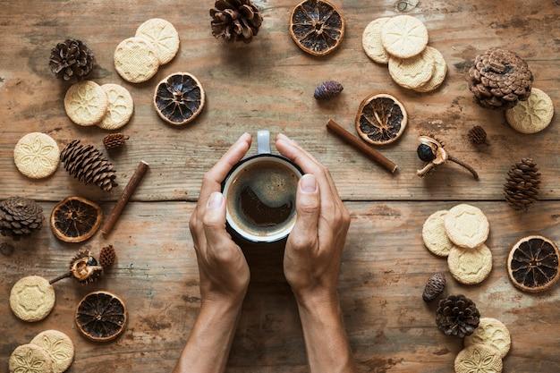 Ernten sie die hände, die nahe tasse kaffee sich wärmen