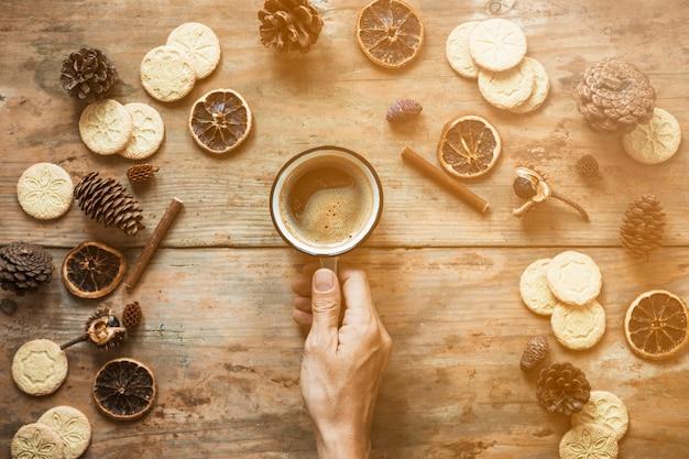 Ernten sie die hand, die kaffee nahe gewürzen hält