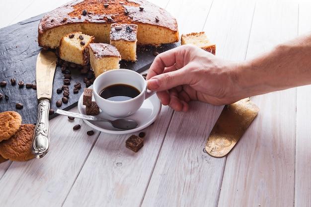 Ernten sie die hand, die kaffee nahe kuchen nimmt