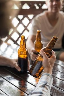 Ernten sie die hand, die kaltes bier nahe freunden hält