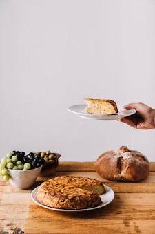Ernten sie die hand, die kuchen nahe lebensmittel hält