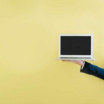 Ernten sie die hand, die laptop auf gelb zeigt