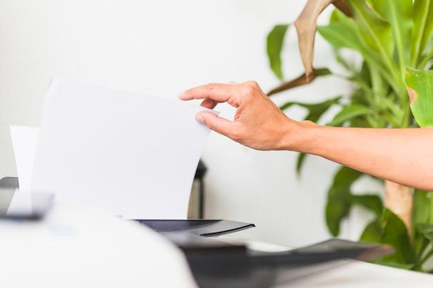 Ernten sie die hand, die papier vom bürodrucker nimmt