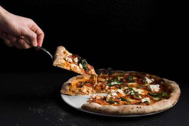 Ernten sie die hand, die scheibe der pizza nimmt