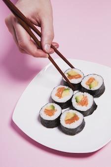 Ernten sie die hand, die sushi von der platte nimmt