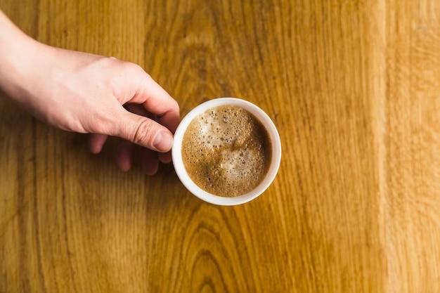 Ernten sie die hand, die tasse kaffee nimmt