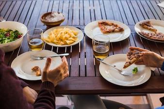 Ernten Sie die Hände des Mannes und der Frau, die zu Mittag essen