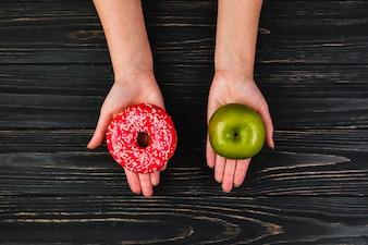 Ernten Sie die Hände, die Donut und Apfel halten
