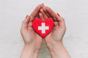 Ernten Sie die Hände, die Herz mit Kreuz halten