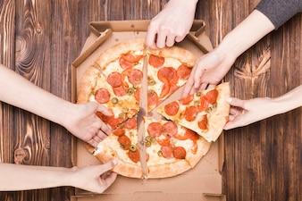 Ernten Sie die Hände, die Pizza nehmen