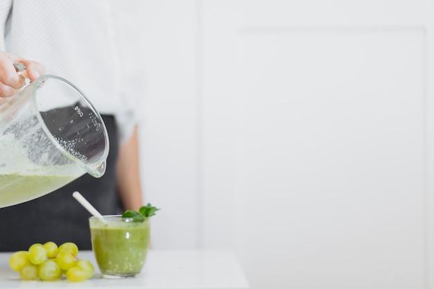 Ernten sie die person, die grünen smoothie zum glas gießt
