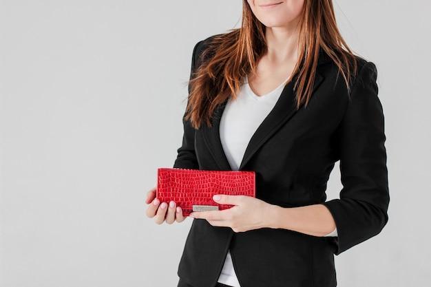Ernten sie foto von lächelnden frauen im schwarzen anzug mit rotem geldbeutel auf grau