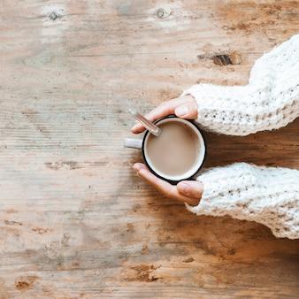 Ernten sie hände in der strickjacke, die nahe heißem kaffee sich wärmt