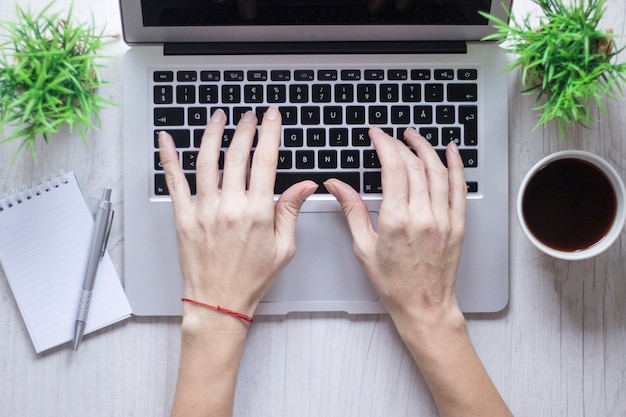 Ernten sie hand unter verwendung des laptops nahe kaffee und notizbuch