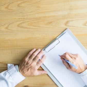 Ernten Sie Hände des Doktorschreibens auf Klemmbrett