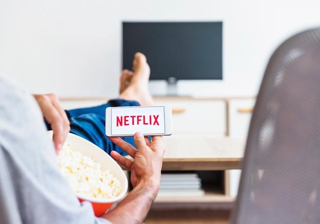 Ernten sie mann mit dem popcorn, das netflix-logo im wohnzimmer demonstriert